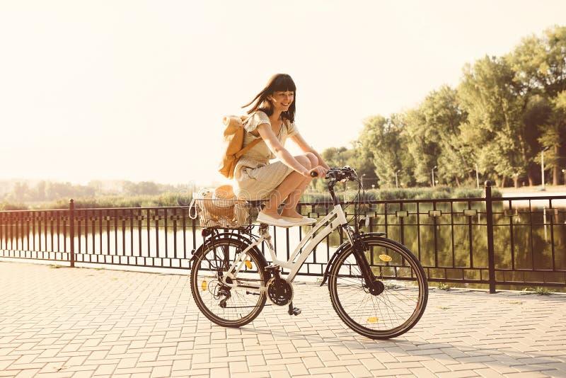 Menina que monta uma bicicleta no parque perto do lago imagens de stock
