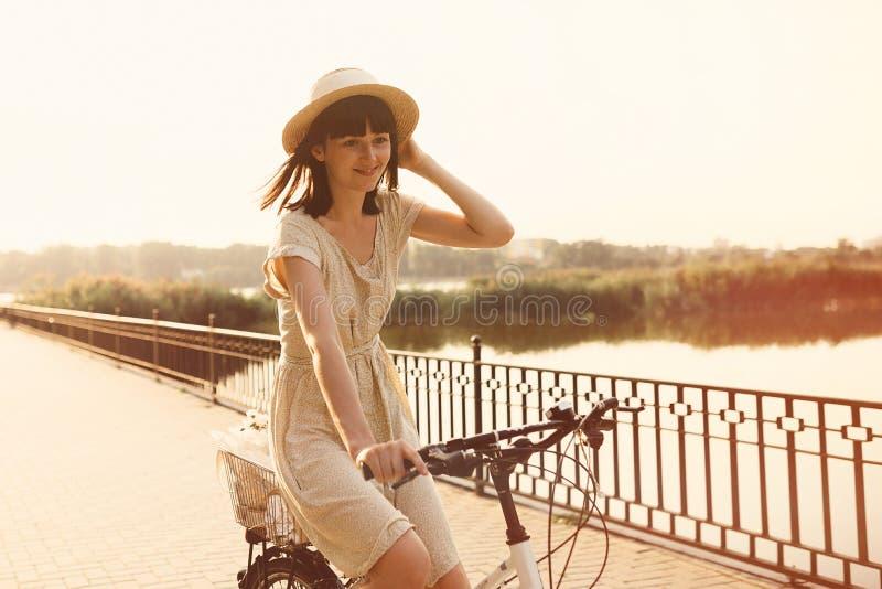 Menina que monta uma bicicleta no parque perto do lago imagem de stock royalty free