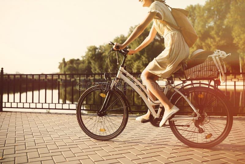 Menina que monta uma bicicleta no parque perto do lago foto de stock royalty free