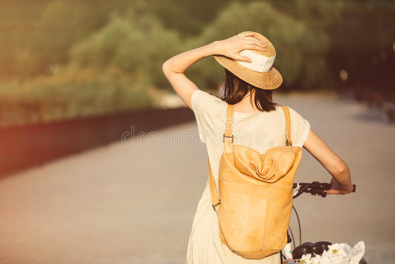 Menina que monta uma bicicleta no parque perto do lago imagem de stock