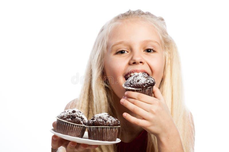 Menina que morde um bolo de chocolate fotos de stock
