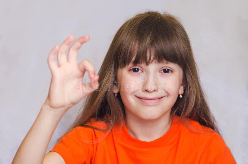 Menina que mostra a mão aprovada fotografia de stock royalty free