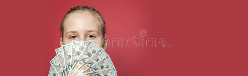 Menina que mostra o dinheiro do dinheiro dos dólares americanos no fundo cor-de-rosa da bandeira imagens de stock