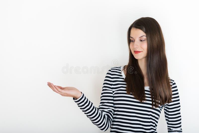 Menina que mostra o espaço vazio da cópia na palma aberta da mão para o texto ou o produto, fundo branco Menina de sorriso que ap fotografia de stock