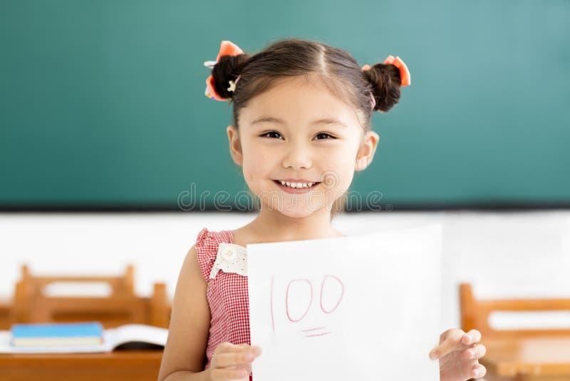 menina que mostra o papel do exame com sinal de adição da na sala de aula fotos de stock