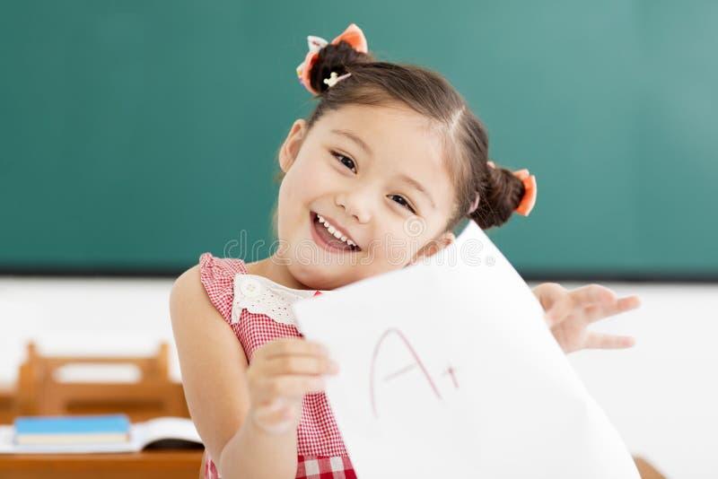 menina que mostra o papel do exame com sinal de adição da na sala de aula imagem de stock