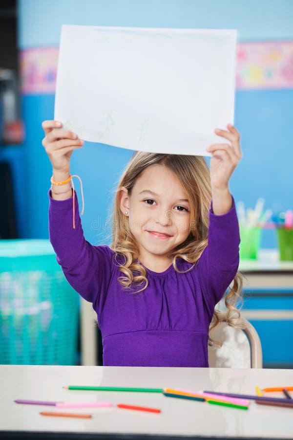 Menina que mostra o papel vazio na mesa fotos de stock royalty free