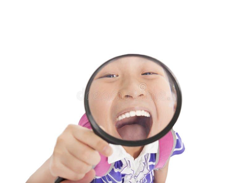 Menina que mostra os dentes pela lente de aumento fotografia de stock