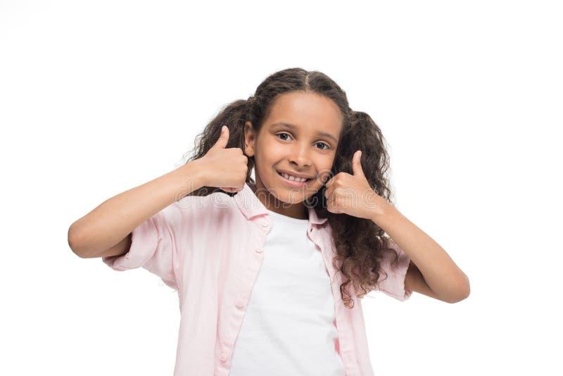 A menina que mostra os polegares levanta o sinal e o sorriso na câmera foto de stock royalty free