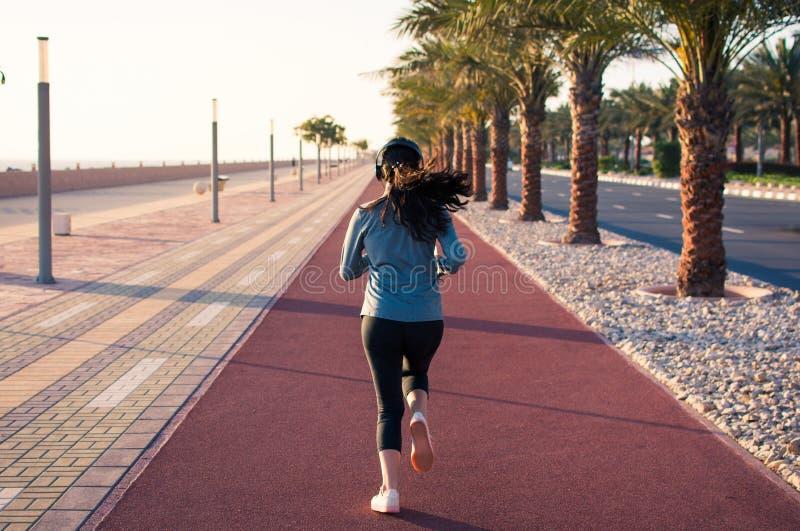 Menina que movimenta-se na pista de atletismo pelo mar imagens de stock royalty free
