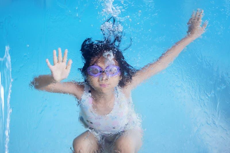 Menina que nada debaixo d'água na associação da nadada fotografia de stock