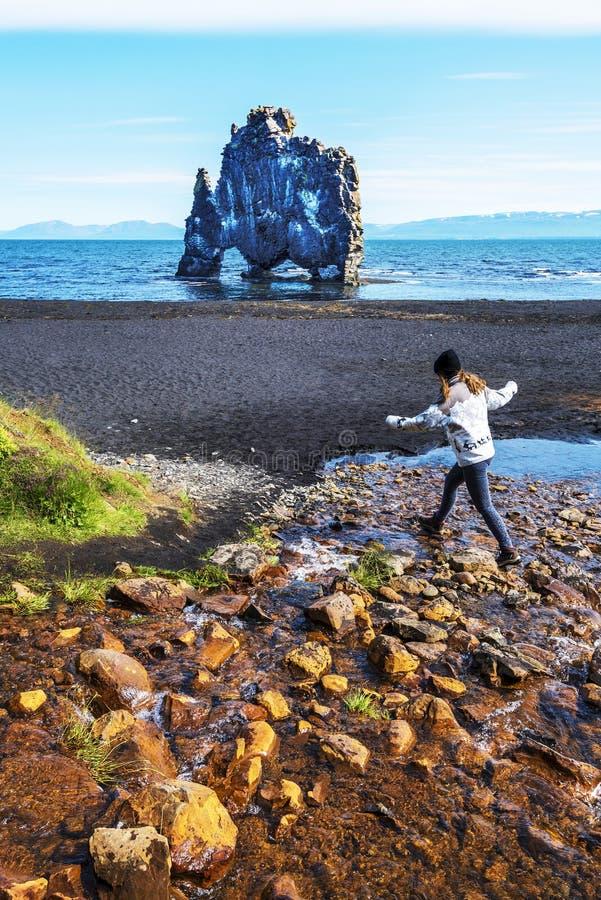 A menina que o adolescente está saltando sobre o córrego da água na beira da baía de Hindisvik em Islândia noroeste, a pilha do b imagem de stock