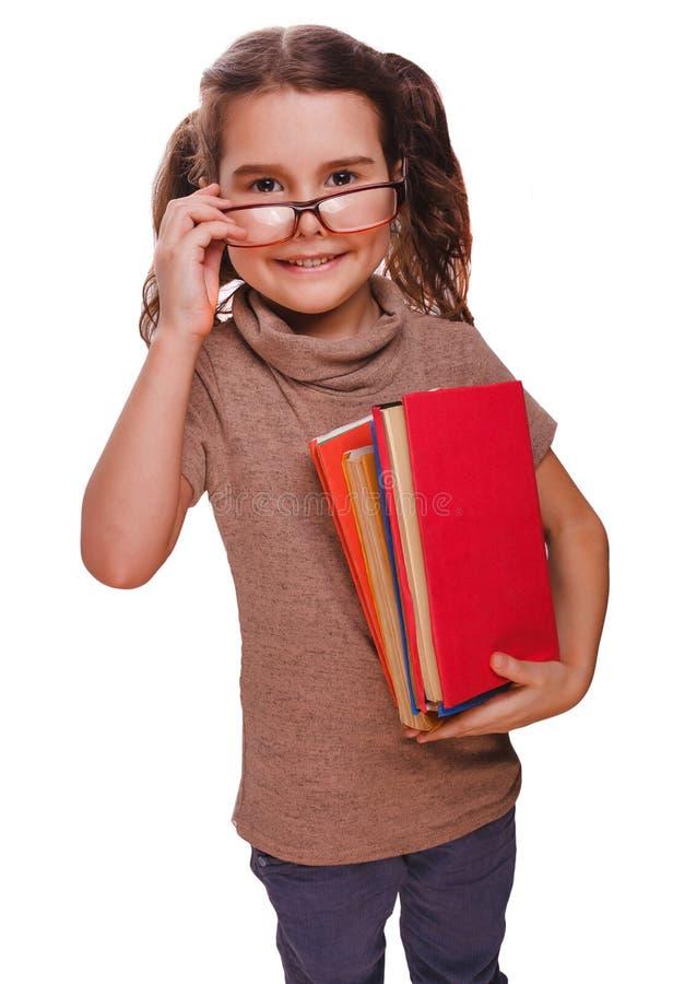 A menina que o bebê moreno dos vidros lê o livro mantém o isolado de sorriso fotografia de stock