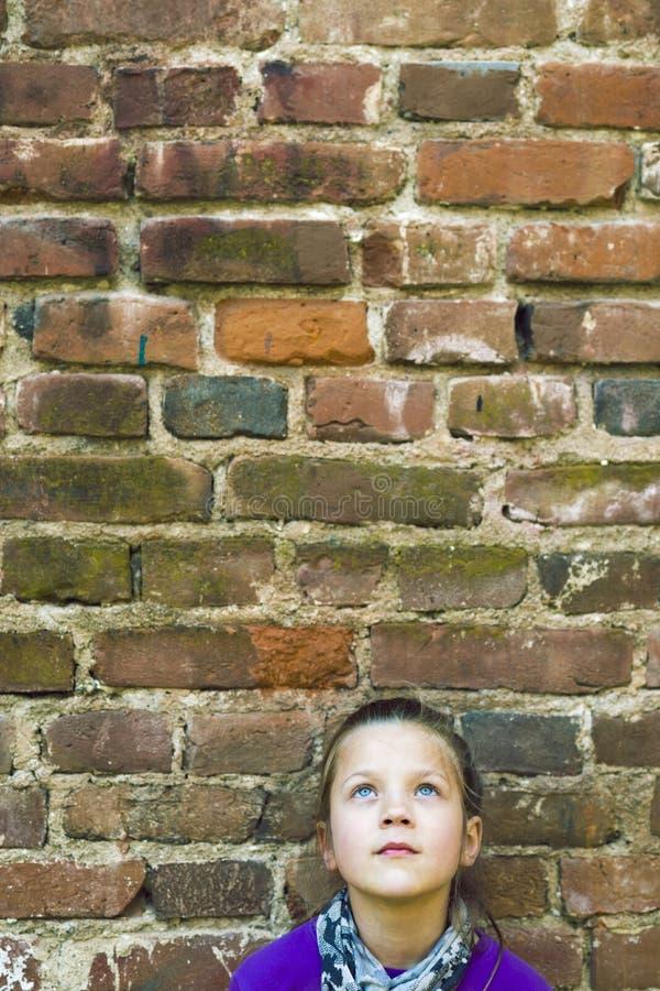 Menina que olha acima a parede imagem de stock