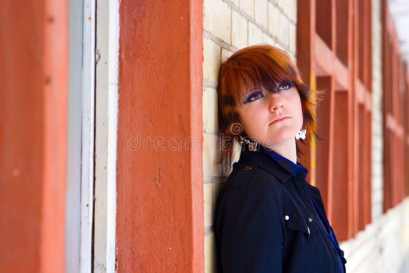 Menina que olha acima perto de uma parede de tijolo fotografia de stock