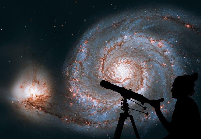 Menina que olha as estrelas com telescópio Galáxia do redemoinho imagens de stock royalty free