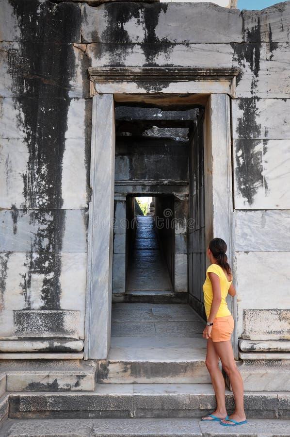 Menina que olha através da porta do templo fotos de stock