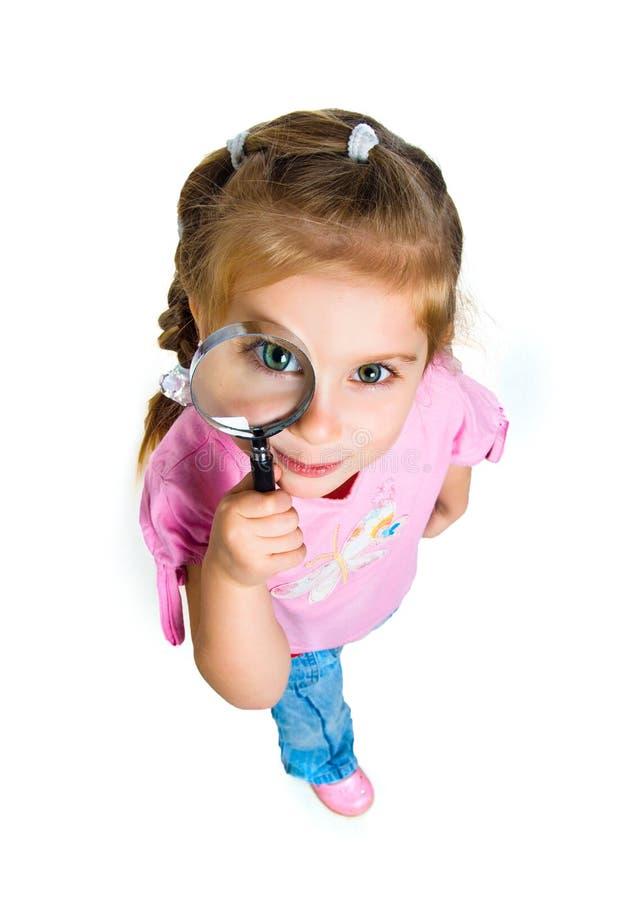 Menina que olha através de um magnifier foto de stock