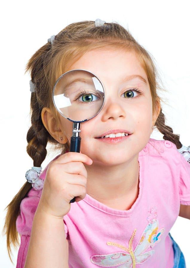 Menina que olha através de um magnifier imagens de stock