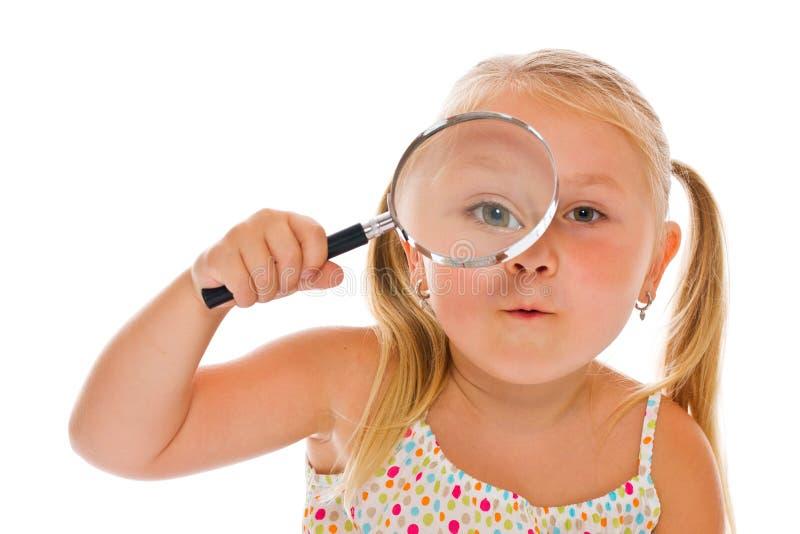 A menina que olha através de uma lupa imagens de stock royalty free