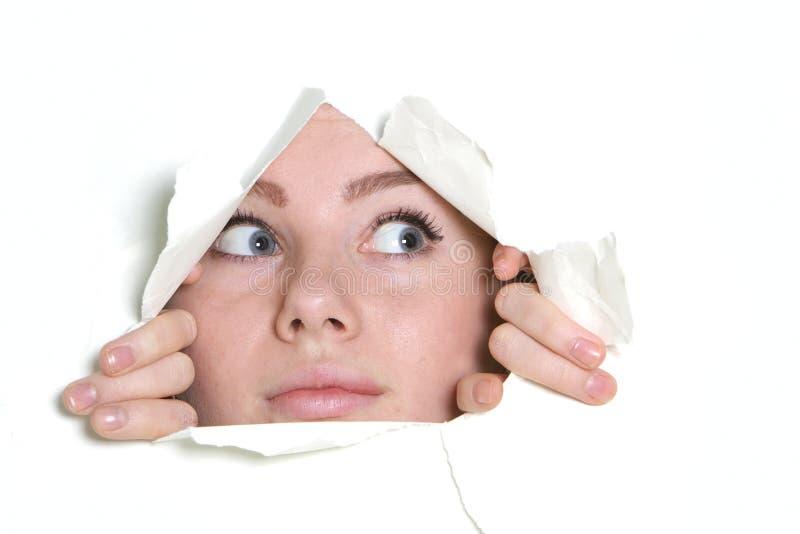 Menina que olha através do furo no papel imagem de stock royalty free