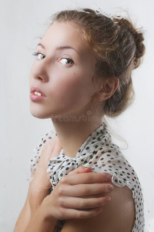 Menina que olha através do indicador após a chuva imagens de stock