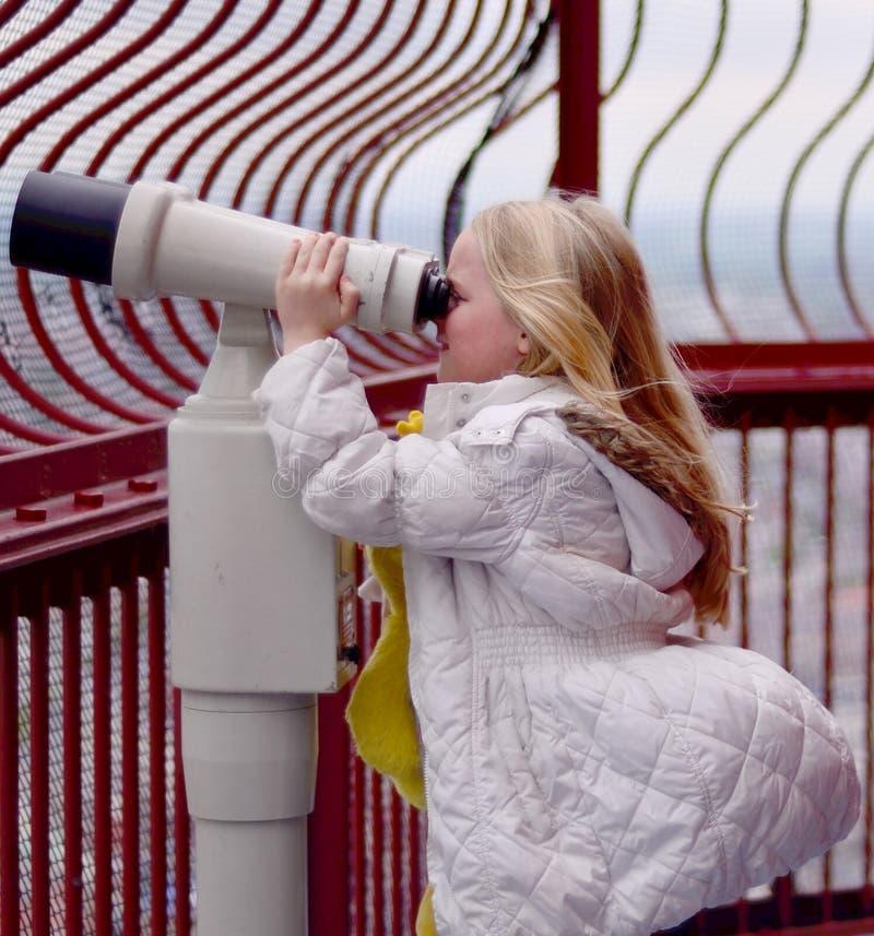 Menina que olha através dos binóculos fotografia de stock