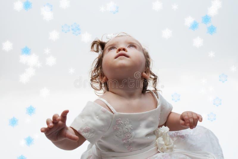 Menina que olha flocos de neve imagens de stock