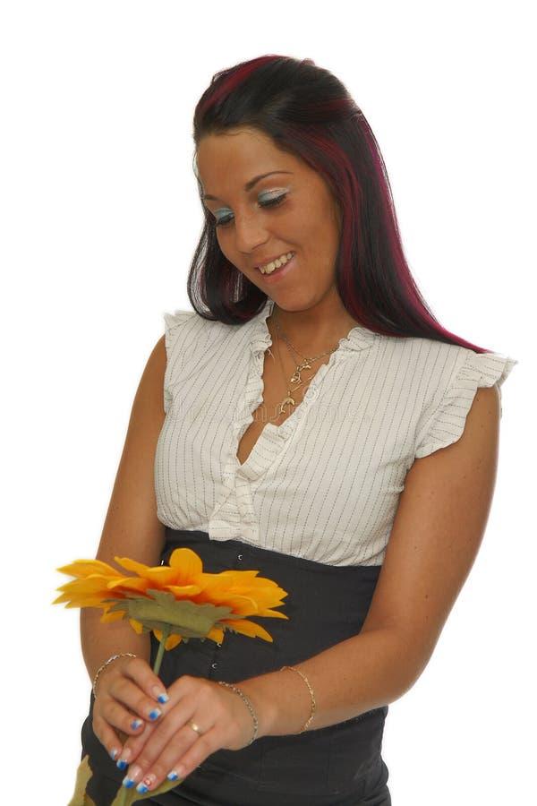Menina que olha a flor amarela foto de stock royalty free