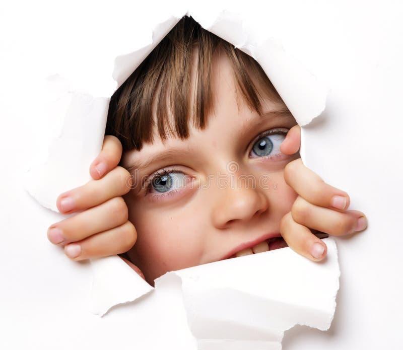 Menina que olha fora de um furo em um papel imagens de stock
