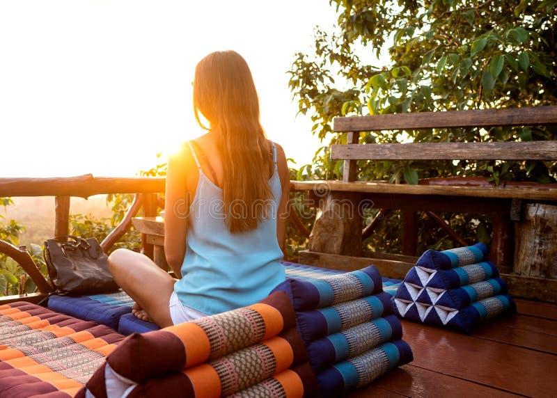 Menina que olha meditar do por do sol imagens de stock royalty free
