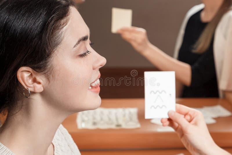 A menina que olha o cartão diz sons foto de stock