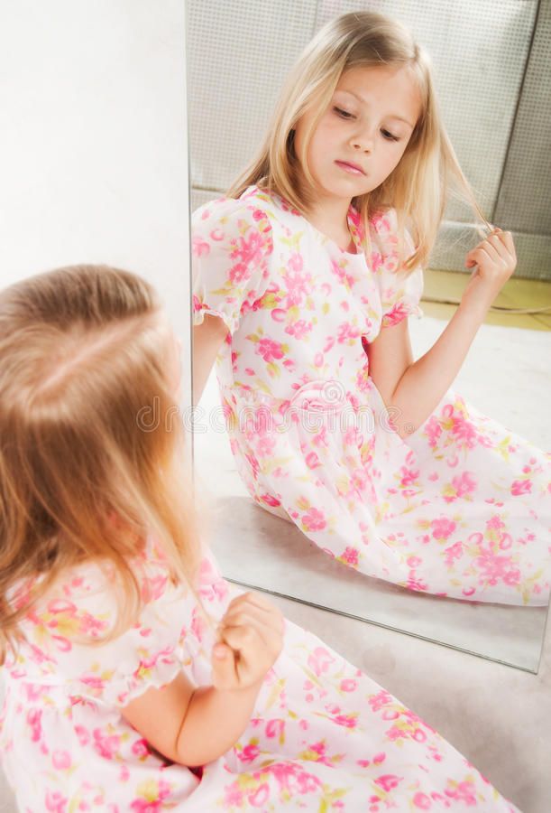Menina que olha o espelho, retrato do estúdio imagens de stock