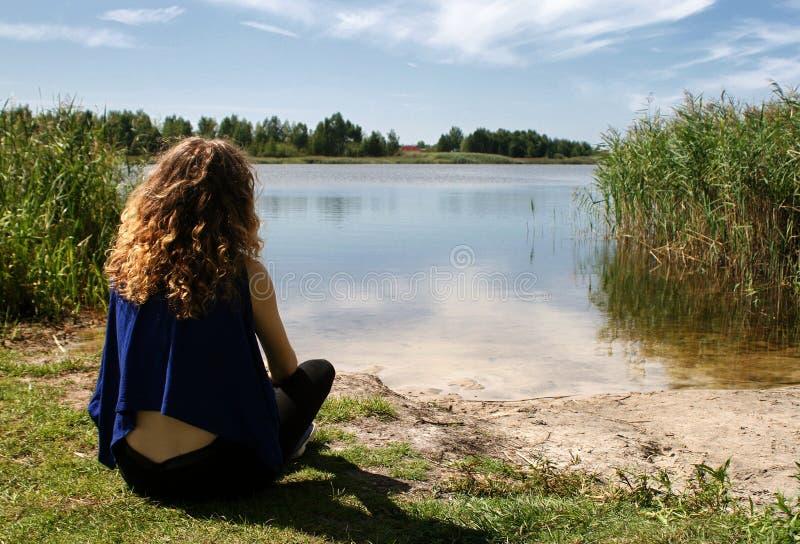 Menina que olha o lago foto de stock