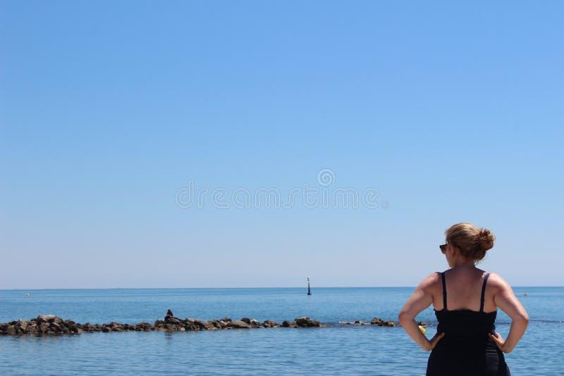 Menina que olha o mar imagens de stock