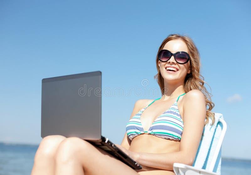 Menina que olha o PC da tabuleta na praia