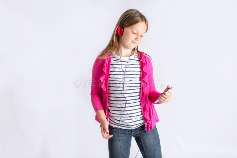Menina que olha o telefone celular com fones de ouvido fotografia de stock royalty free