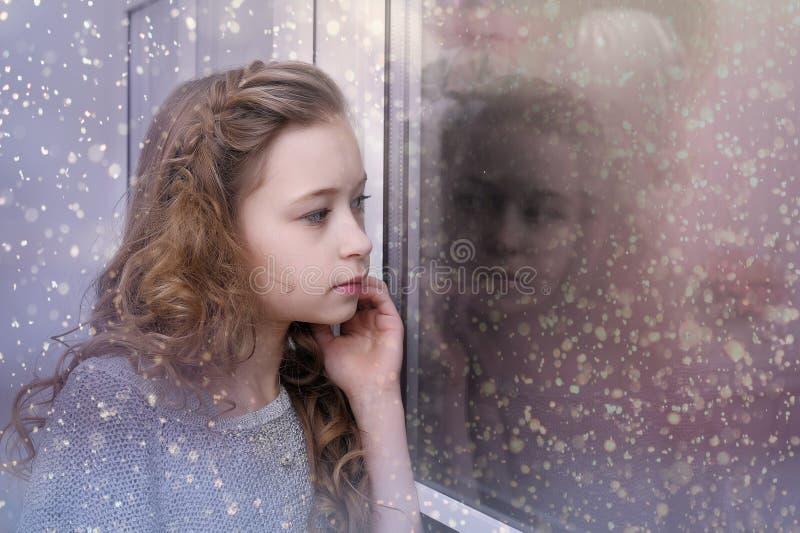 Menina que olha para fora a janela fotos de stock