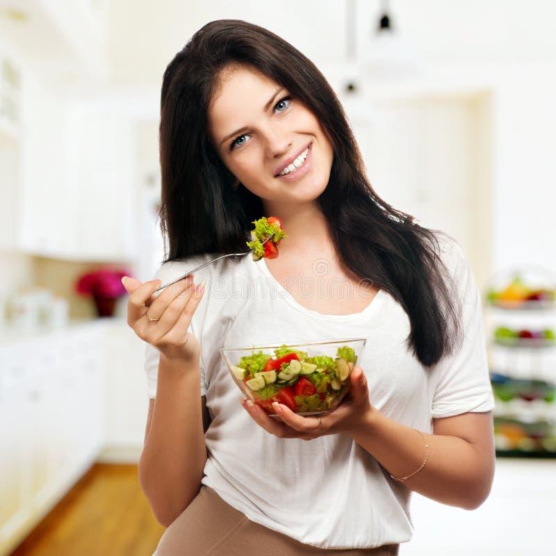 Menina que olha positiva e que guarda gritar com salada imagem de stock