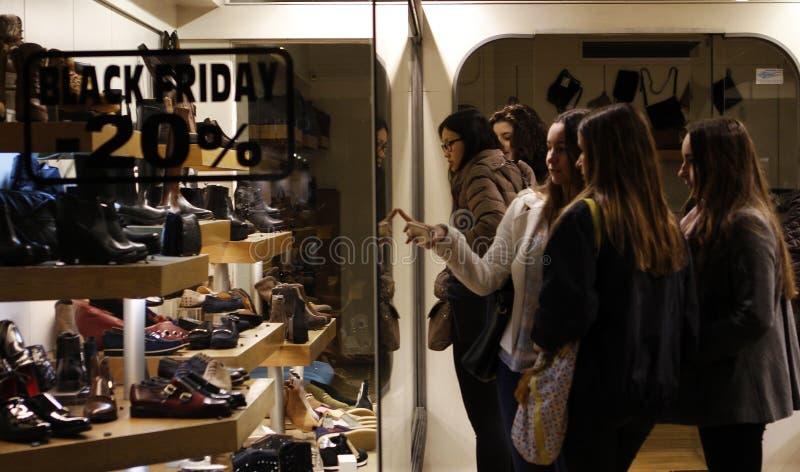 Menina que olha sapatas em uma loja fotos de stock