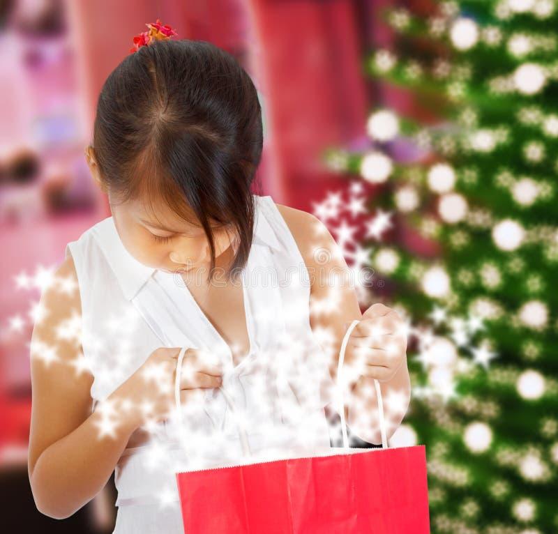 Menina que olha seu presente Sparkling do Natal imagem de stock