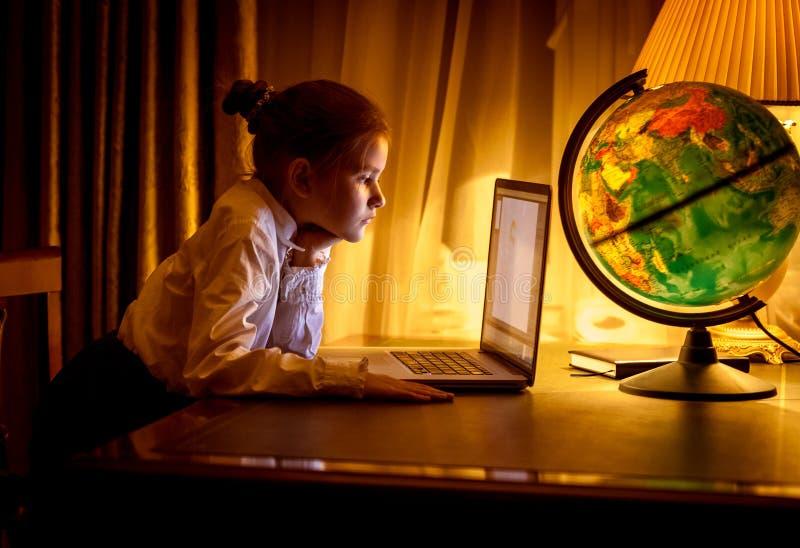 Menina que olha a tela do portátil na sala escura imagem de stock