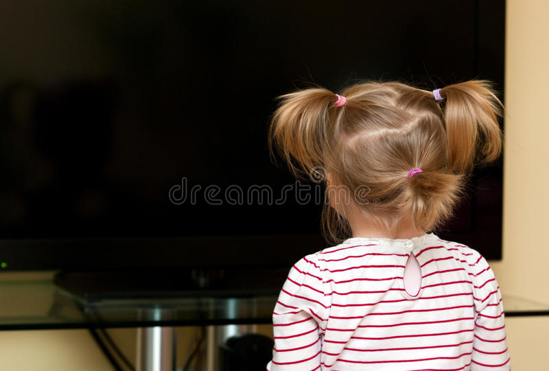 Menina que olha a tevê em branco foto de stock royalty free