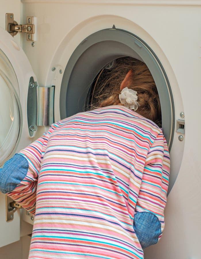 Menina que põe a cabeça na máquina de lavar fotografia de stock royalty free