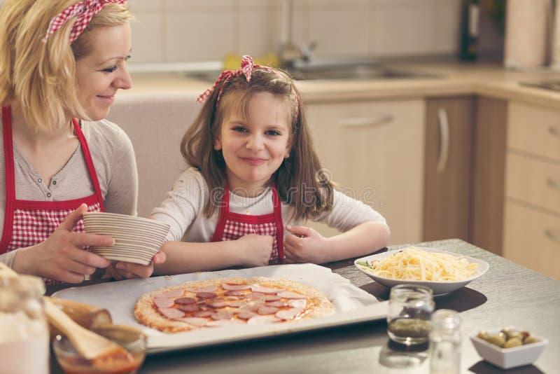 Menina que põe o salame sobre a massa da pizza fotos de stock royalty free