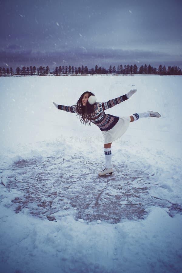 Menina que patina fora no inverno foto de stock