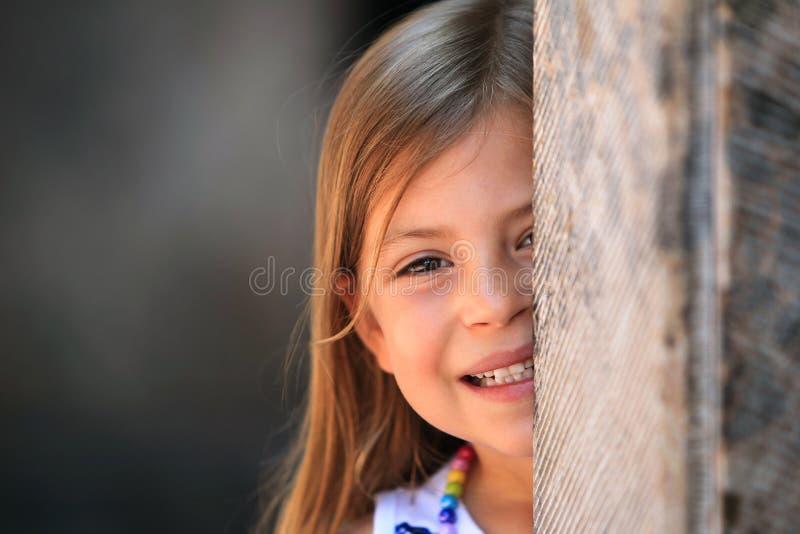 Menina que peeping da coluna de trás fotos de stock royalty free