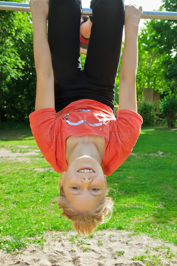 Menina que pendura upside-down imagens de stock royalty free