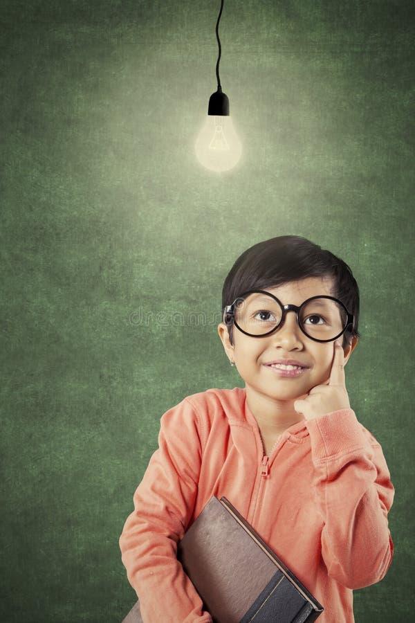Menina que pensa uma ideia na sala de aula foto de stock royalty free