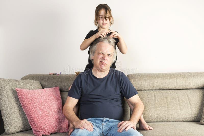 Menina que penteia e que faz a tranças seu paizinho em casa foto de stock royalty free
